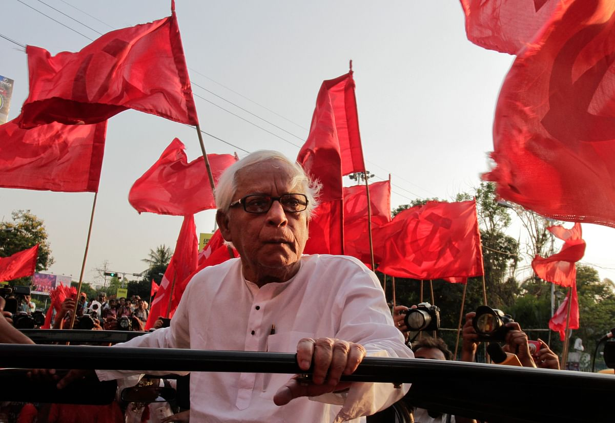Communist Party of India-Marxist (CPI-M) leader Buddhadeb Bhattacharya, surrounded by party flags travels on an open hood vehicle during an election rally, in Kolkata.(Photo: AP)