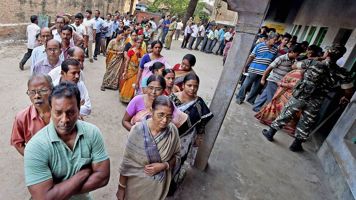 Voters stand in a queue to cast vote at a polling booth during 4th phase of the West Bengal assembly polls in Howrah on Monday. (Photo: PTI)