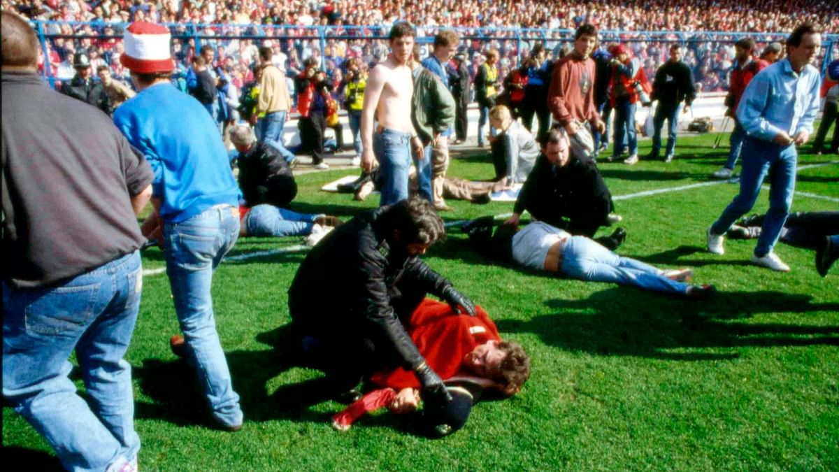 In this April 15, 1989 file photo police, stewards and supporters tend and care for wounded supporters. (Photo: AP)