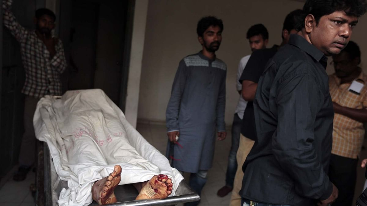 The body of Xulhaz Mannan, who was stabbed to death by unidentified assailants, being carried out of a hospital morgue in Dhaka. (Photo: AP)