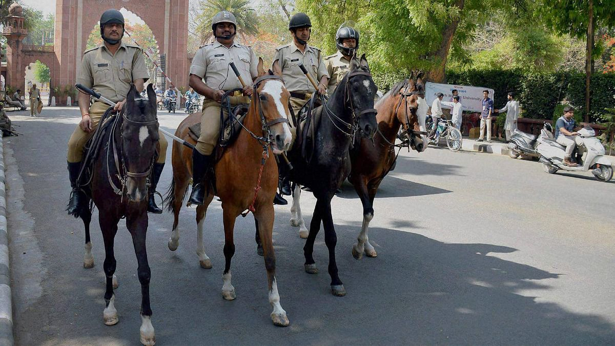Police force deployed infront of  Aligarh Muslim University gate after the clashes between two groups at University campus,  in Aligarh on Sunday. (Photo: PTI)