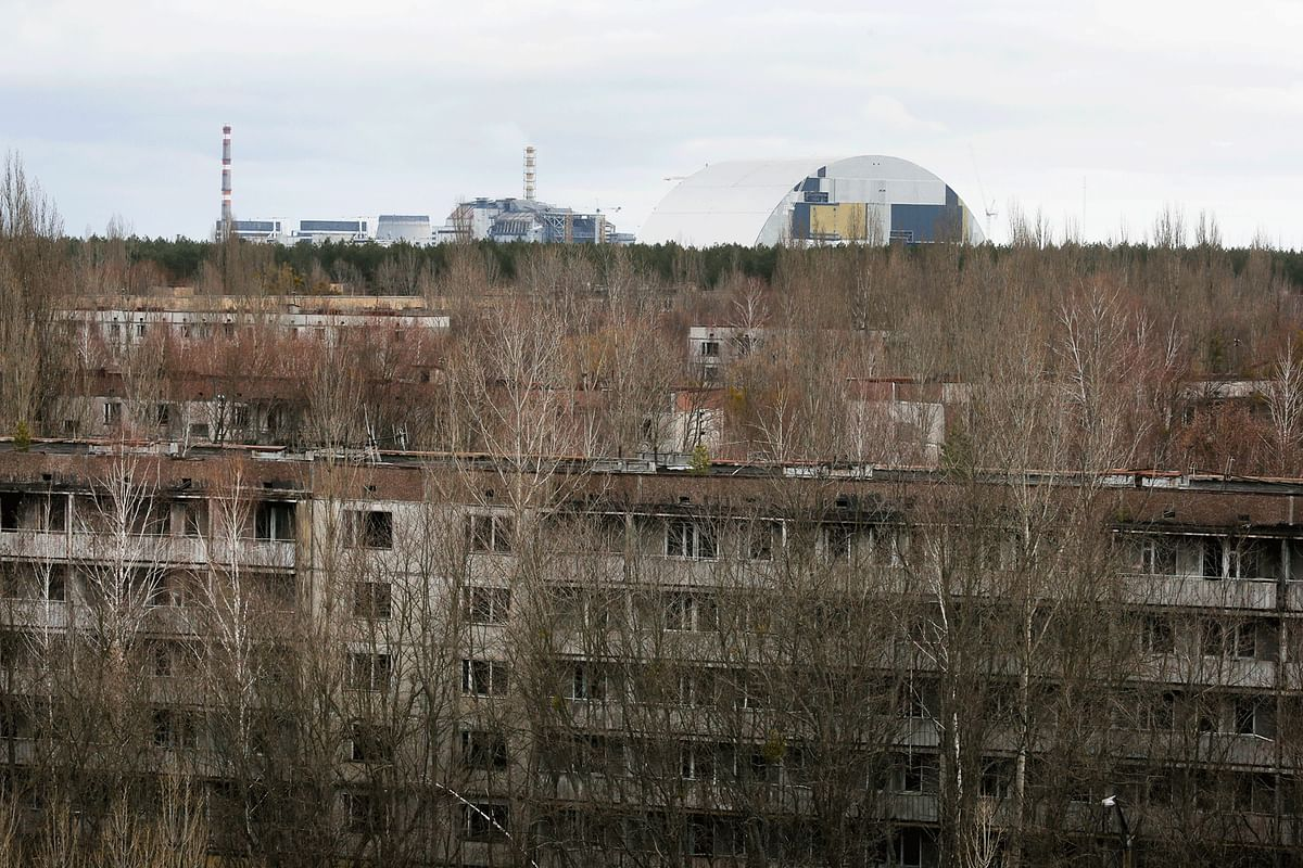 Trees grow into and onto derelict apartments in Pripyat, as the damaged reactor stands in the background, with the under-construction containment shield. (Photo: AP)