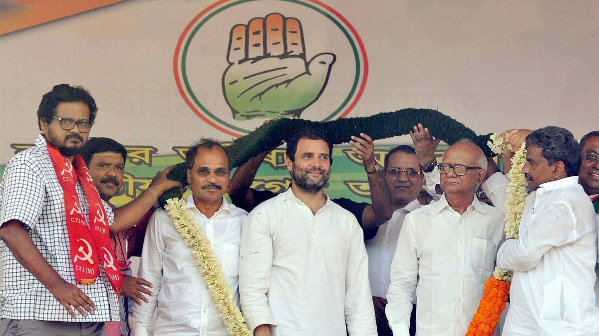 Congress Vice-President Rahul Gandhi being garlanded by CPI(M)-Congress joint candidates Anjan Bera (L) and Santosh Pathak (R)  during an election campaign rally in Howrah on Saturday. To Rahul's left is West Bengal Congress chief and Lok Sabha MP Adhir Ranjan Chowdhury. (Photo: PTI)