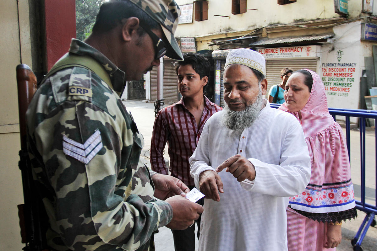 An Indian paramilitary soldier checks the identity of voters outside a polling booth during the third phase of voting in the West Bengal state Assembly elections. (Photo: AP)