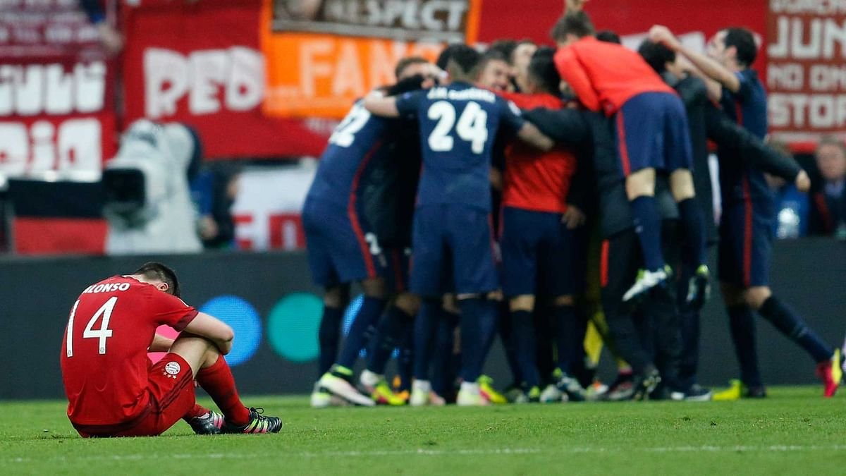 Bayern's Xabi Alonso sits on the pitch as Atletico players celebrate after advancing to the final  of the Champions League. (Photo: AP)