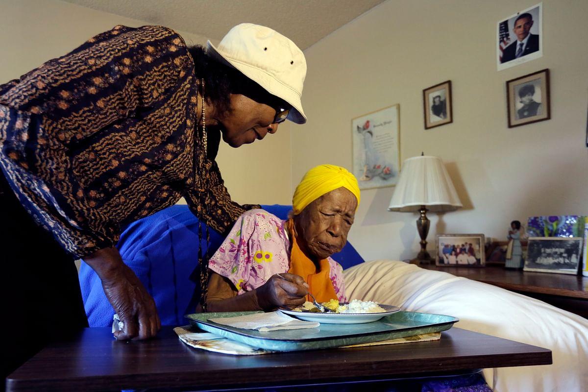 Lois Judge  helps her aunt Susannah Mushatt Jones,right, during breakfast in Jones' room in New York, 2015. (Photo: AP)