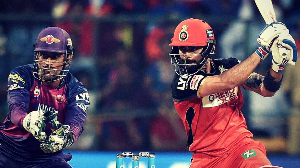 Virat Kohli plays a shot as MS Dhoni looks on. (Photo: PTI)