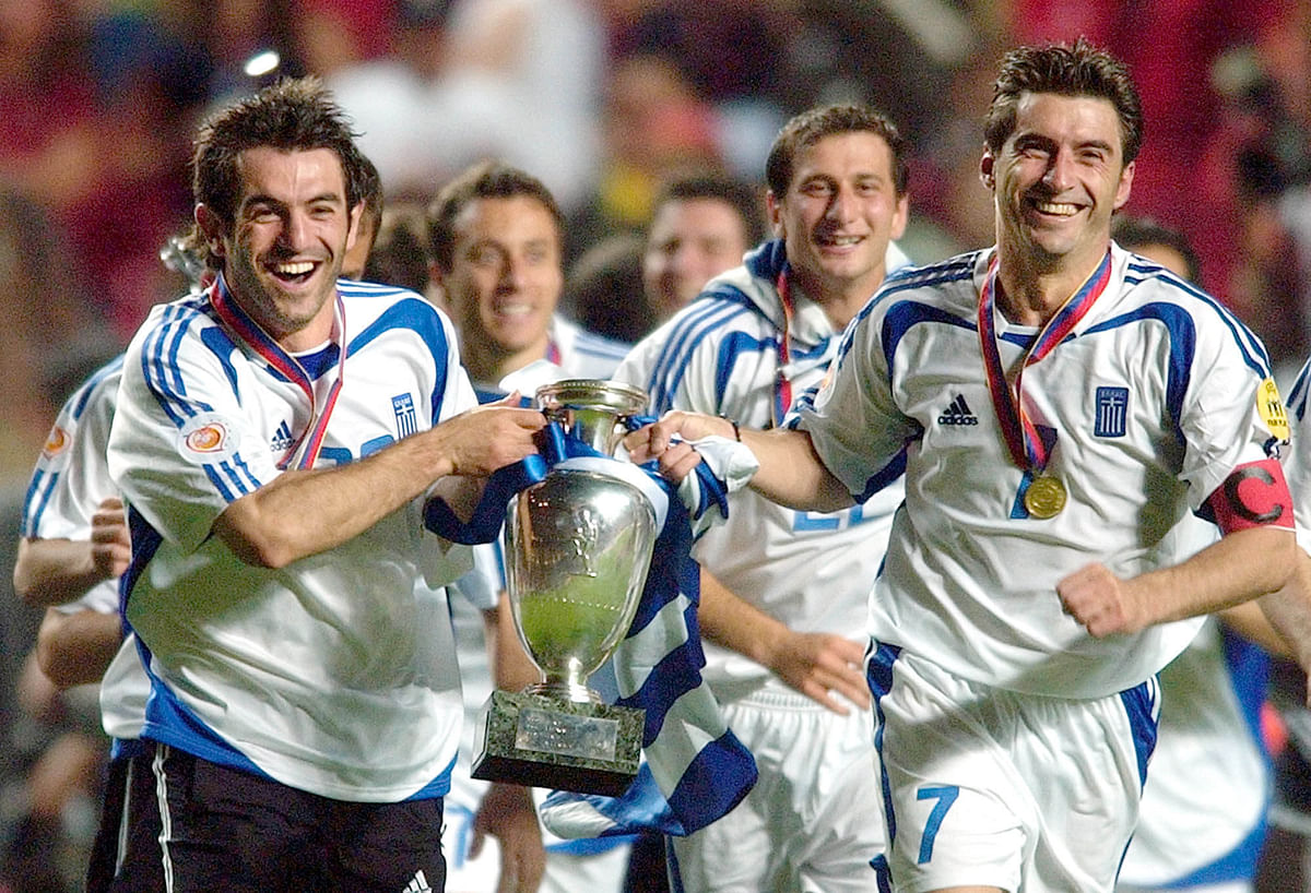 In this Sunday, July 4, 2004 file photo Georgios Karagounis, left, and Theodoros Zagorakis of Greece run with the trophy after their team's 1-0 victory over Portugal in the Euro 2004 soccer championship final. (Photo: AP)<a></a>