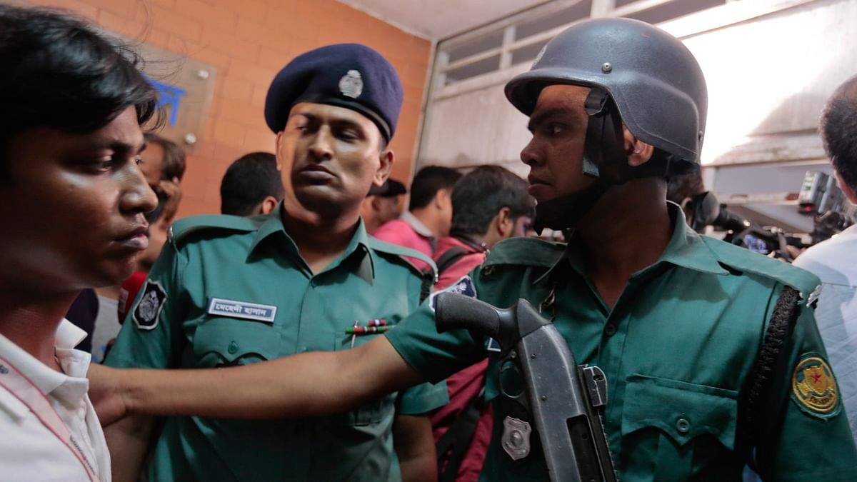 Bangladeshi policemen try to control the crowd of onlookers at a building where Xulhaz Mannan and his friend Tonoy Mahbub were found stabbed to death in Dhaka, Bangladesh, Monday 25 April 2016. (Photo: AP)