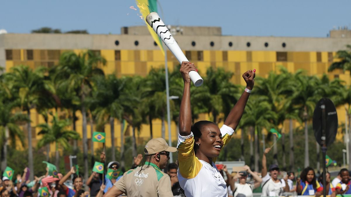 Brazilian volleyball player Fabiana Claudino holds the Olympic torch after the torch lighting ceremony at Planalto presidential palace in Brasilia. (Photo: AP)