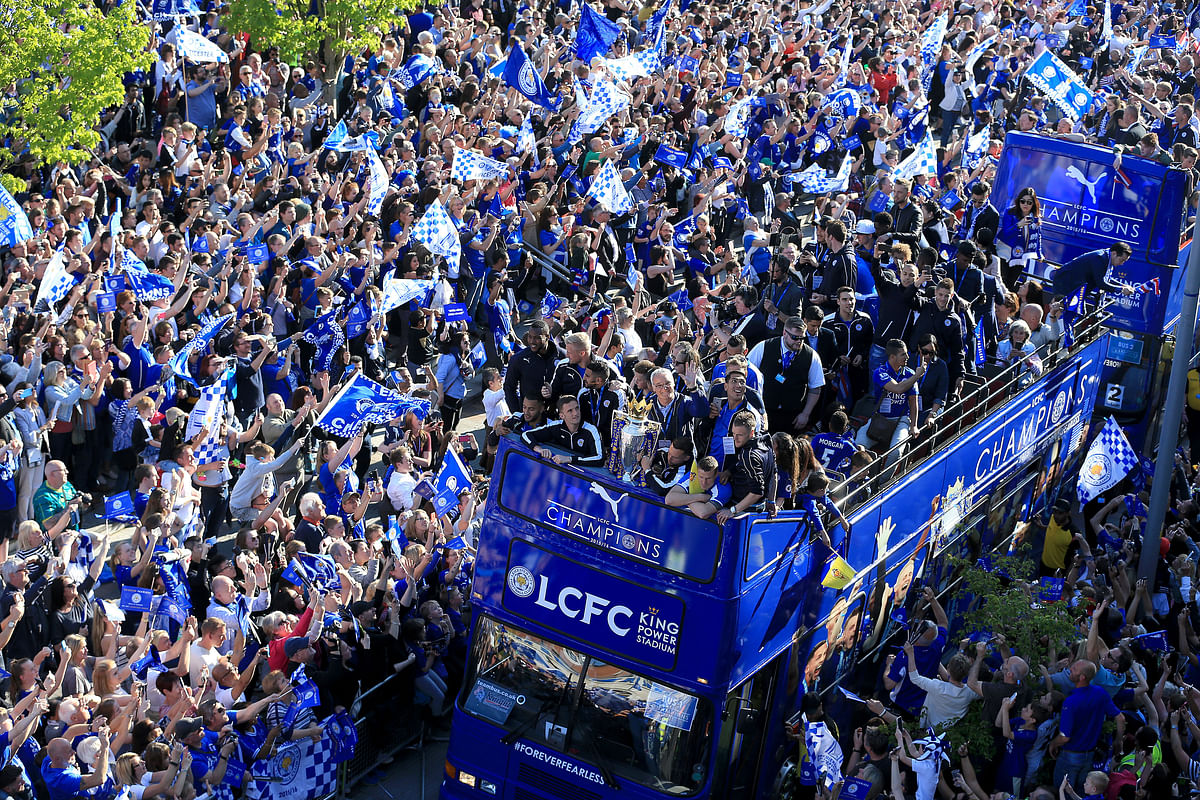Leicester City players and staff celebrate with the trophy after winning the English Premier League during an open top bus parade through Leicester city centre. (Photo: AP)