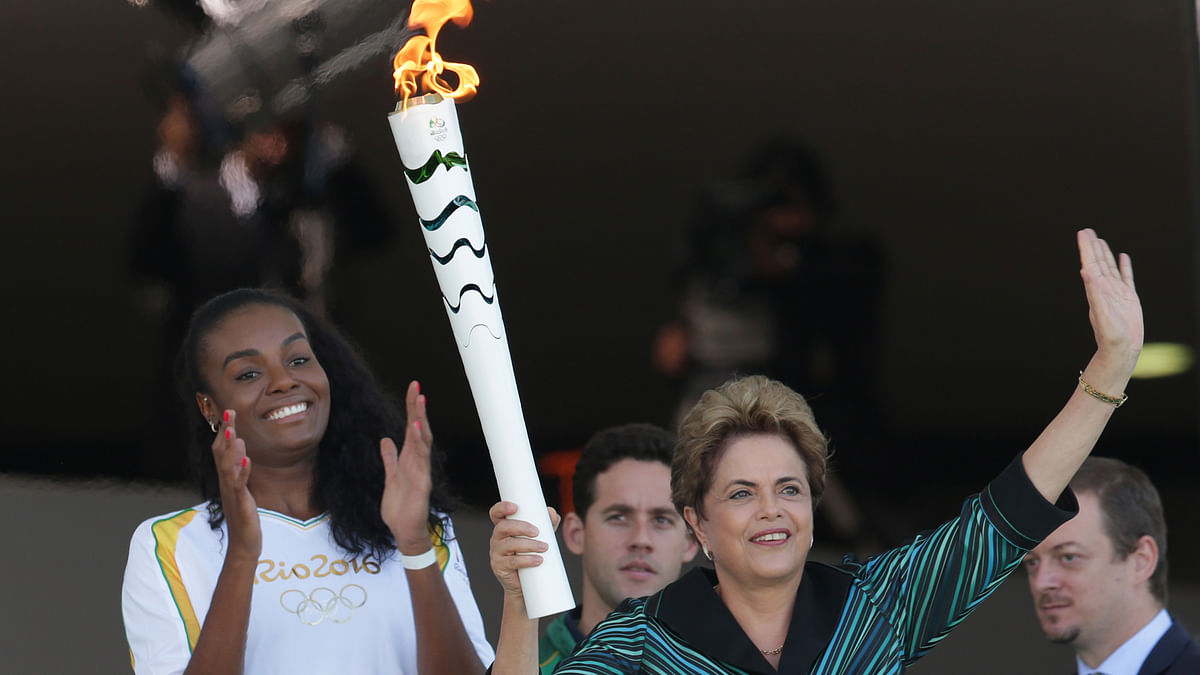 Brazil's President Dilma Rousseff holds the Olympic torch as Brazilian volleyball player Fabiana Claudino applauds after the torch was ignited at Planalto presidential palace in Brasilia (Photo: AP)