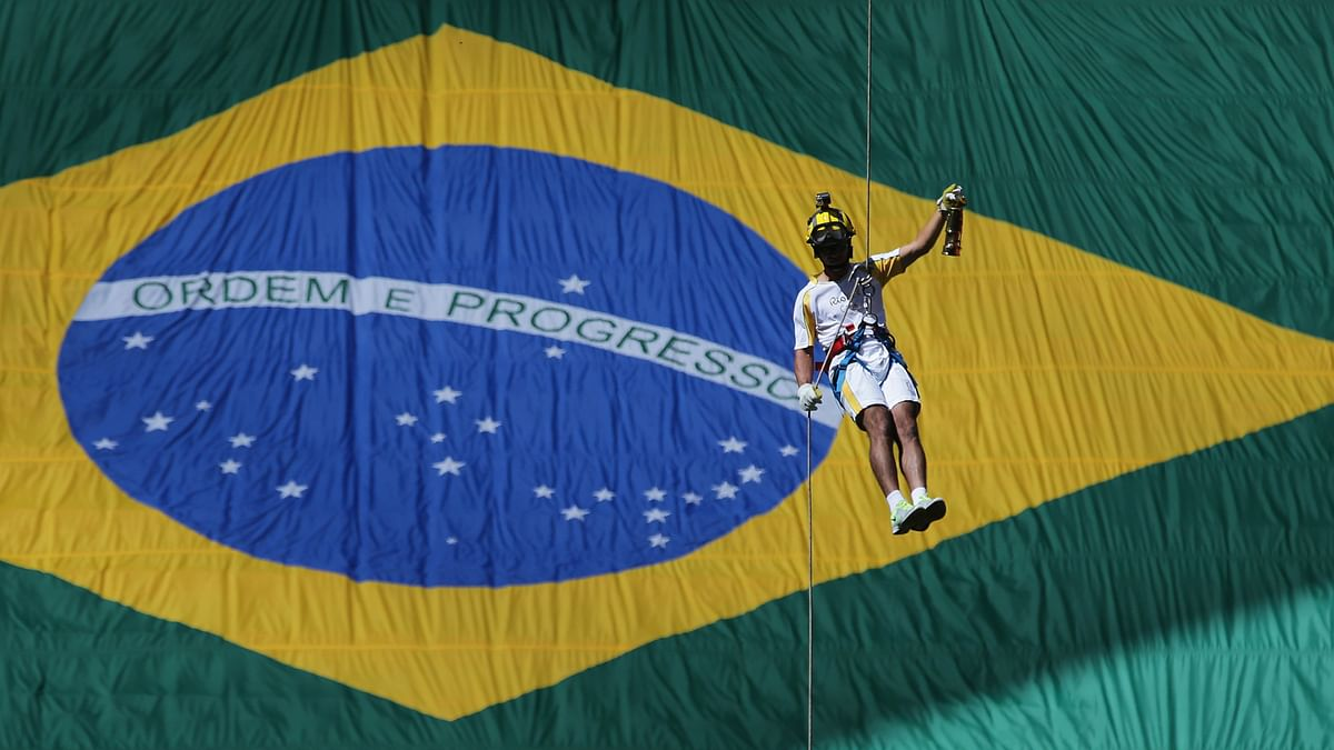 Brazil's athlete Hudson Alves rappels down in front of a huge Brazilian flag, carrying the Olympic flame in a lantern during the torch relay in Brasilia. (Photo: AP)