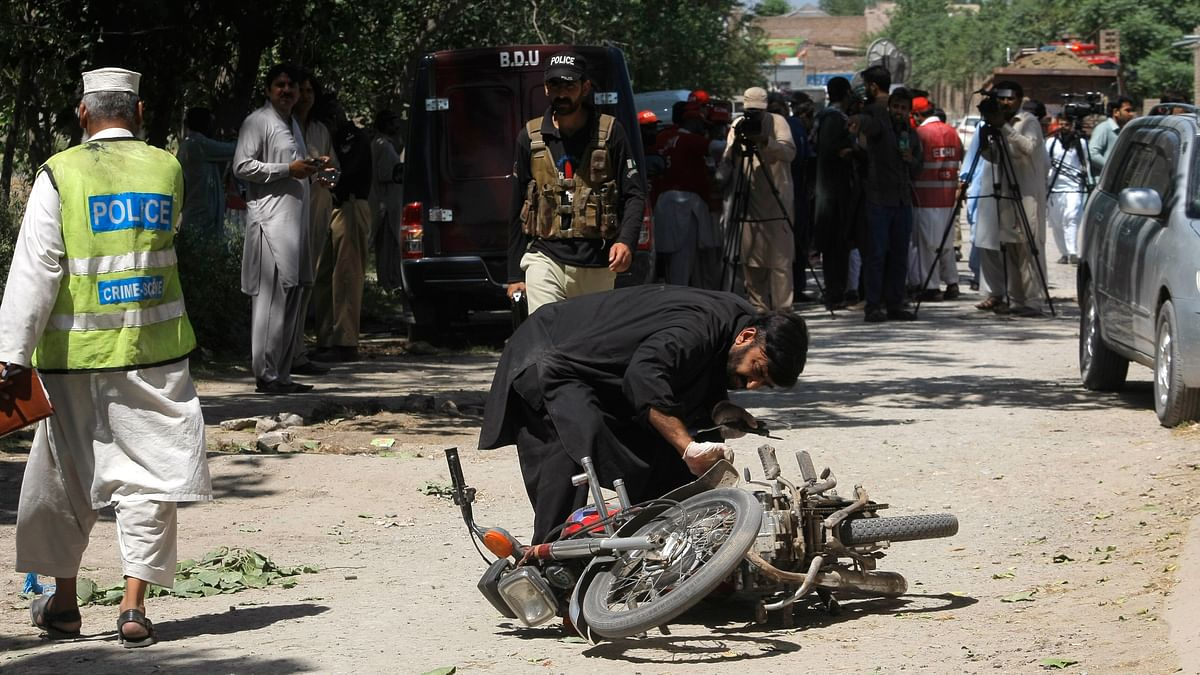 A Pakistani security official inspects a motorcycle following the blast in Peshawar, Pakistan. (Photo: AP)