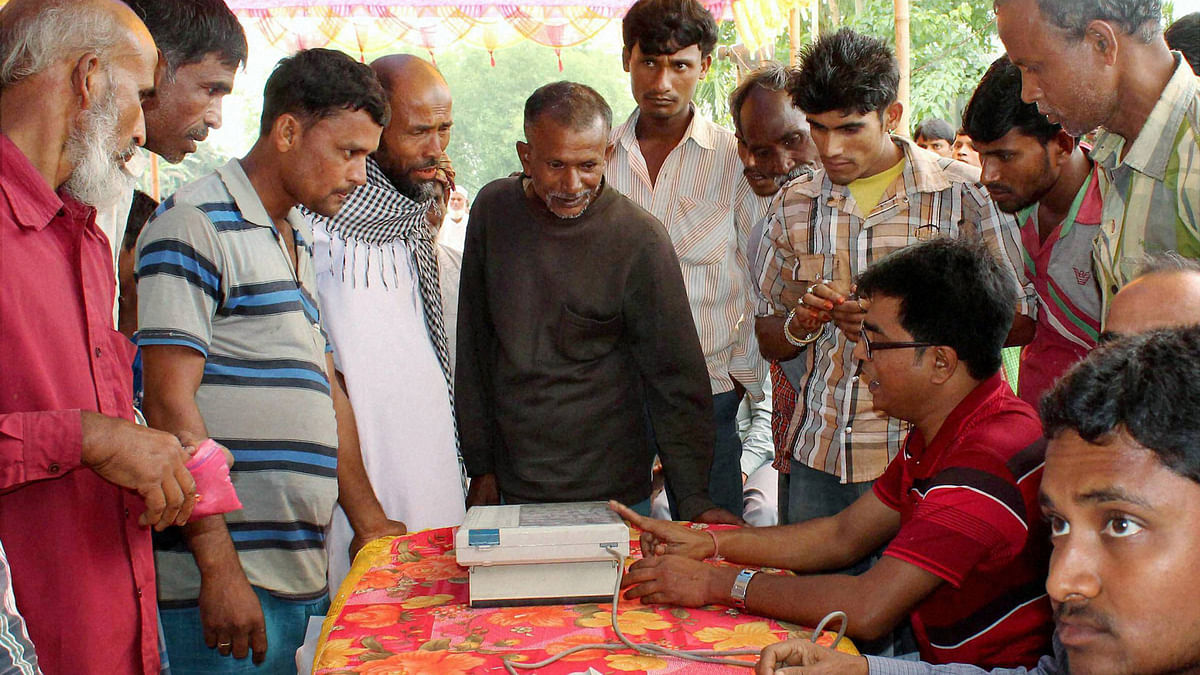 Election Commission officials demonstrating the handling of EVM.