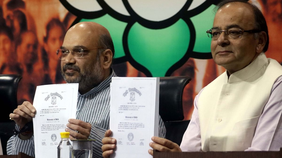 Finance Minister Arun Jaitley and BJP chief Amit Shah holding up Prime Minister Narendra Modi's degrees in New Delhi on 9 May. (Photo: IANS)