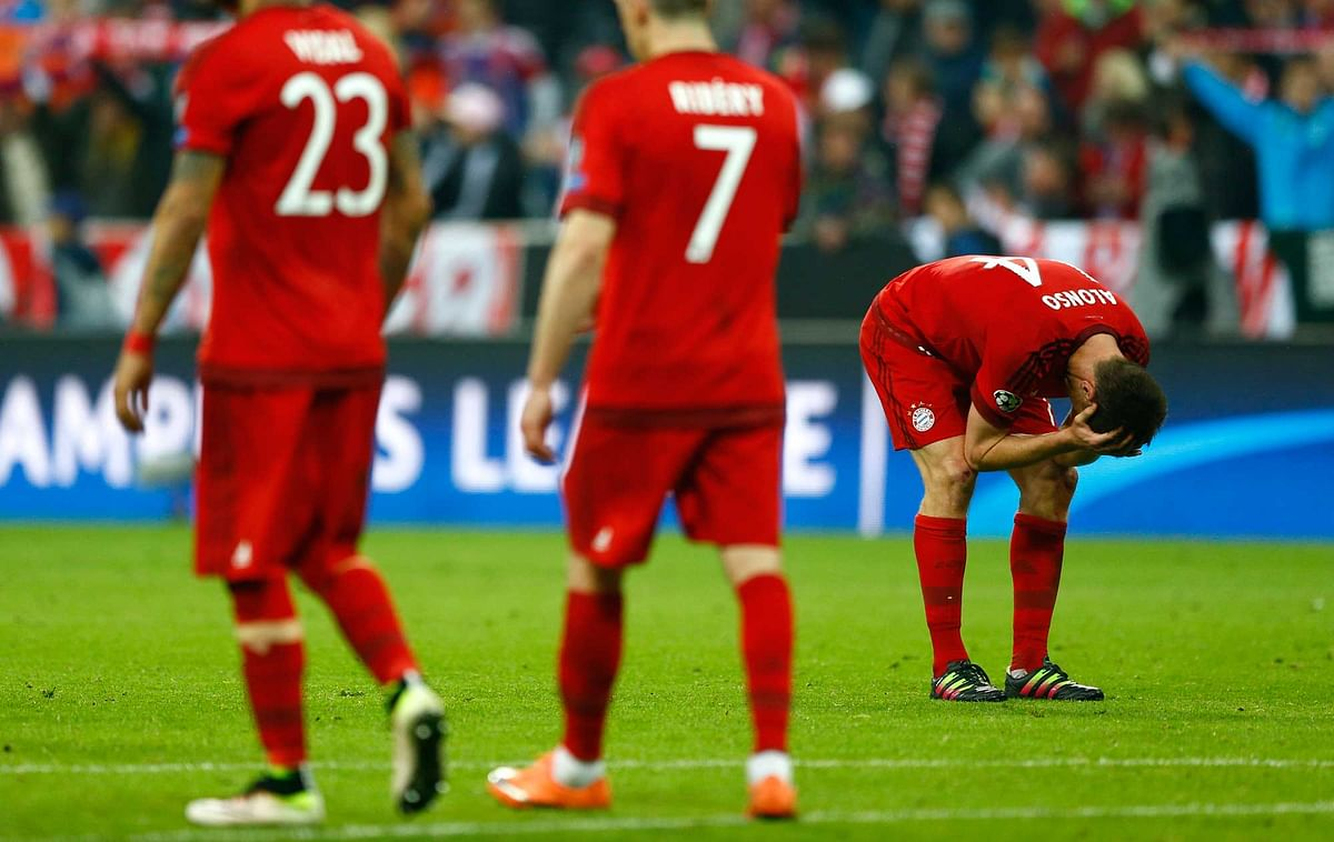 Bayern's players leave the pitch as Atletico players celebrate after advancing to the final after the final whistle. (Photo: AP)