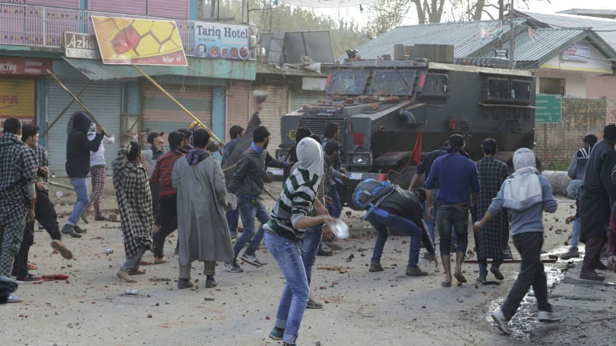 People pelt stones on an army vehicle a day after two people were killed in army firing in Handwara of Jammu and Kashmir, 13 April 2016. (Photo: IANS)