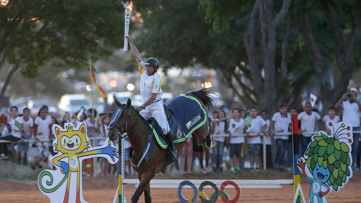 Jose Batista holds the Olympic torch aloft as he rides his horse over the obstacle course. (Photo: AP)