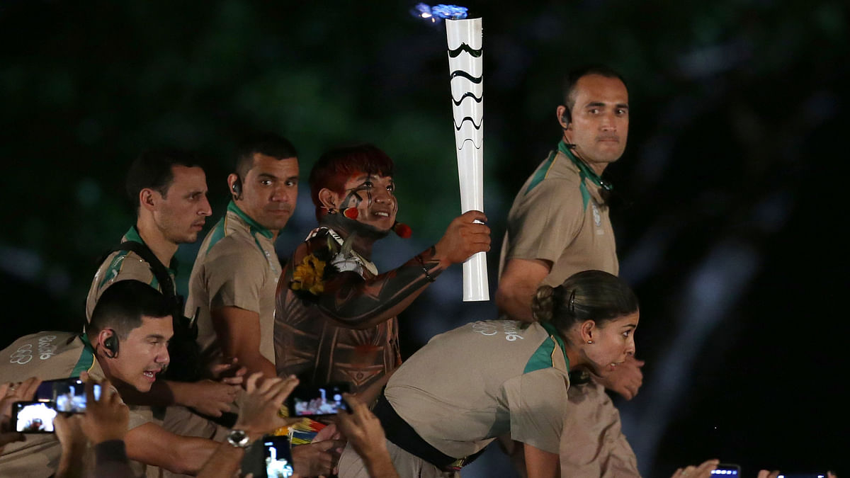 Brazil's Indian athlete Kamukaika Lappa of the Yawalapiti ethnic group carries the Olympic torch during the torch relay in Brasilia. (Photo: AP)