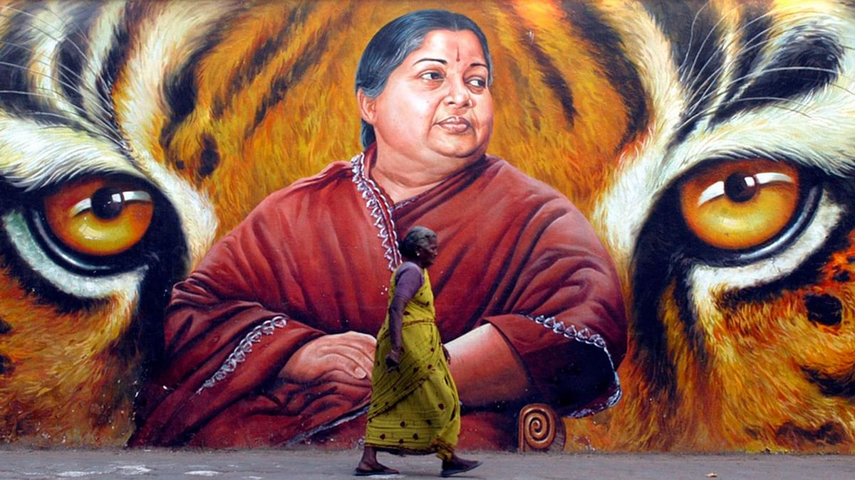 A woman walks past a poster of Tamil Nadu Chief Minister J Jayalalithaa.