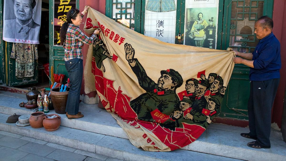 """Vendors unfurl a banner from 1969 depicting former Chinese leader Mao Zedong as he """"inspects the great army of the Cultural Revolution""""."""