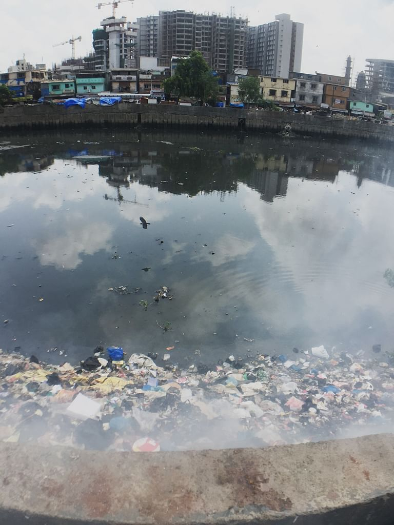 Burning trash piled up on the Mithi river, reaching the boundary wall. In the distance, Gyaneshwar Nagar, Bandra (East) slums, with the swanky Bandra-Kurla Complex, in the background. (Photo: <b>The Quint</b>/Pallavi Prasad)