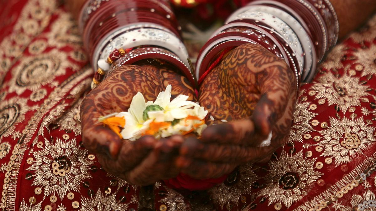 A bride holds flowers with <i>mehendi</i> on her hands during her wedding ceremony. (Photo: Reuters)
