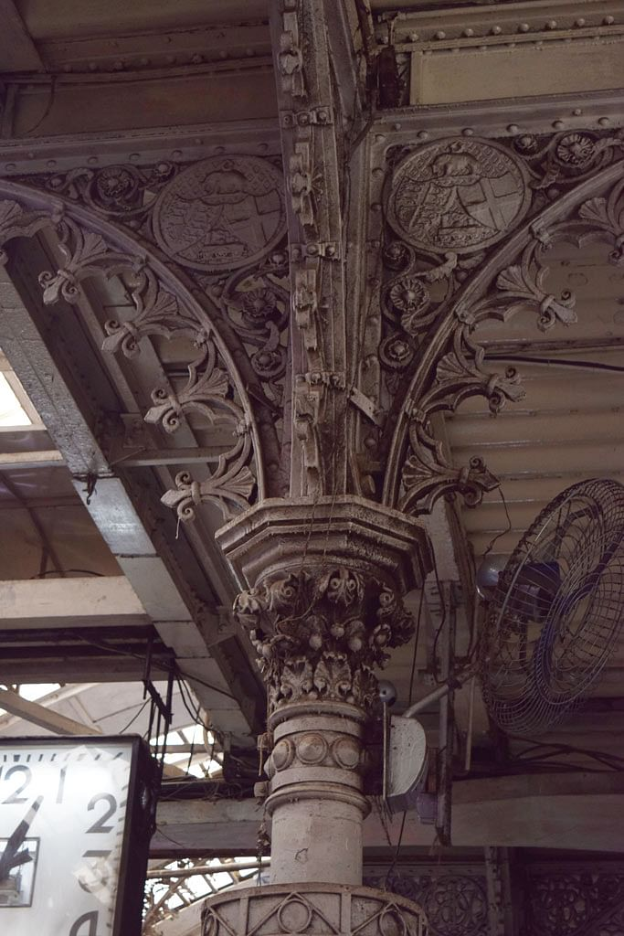 Owls, florets, symmetrical patterns and the coat of arms made of wrought iron sit in plain sight above the pillars on the heavily crowded platforms at VT. (Photo: <b>The Quint</b>/Pallavi Prasad)