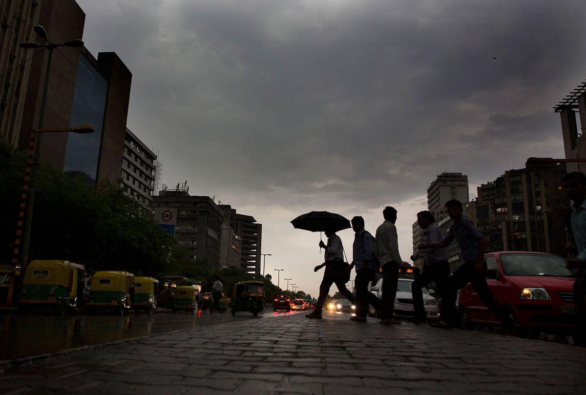 Indian commuters walk home in the rain in New Delhi.  (Photo: AP)