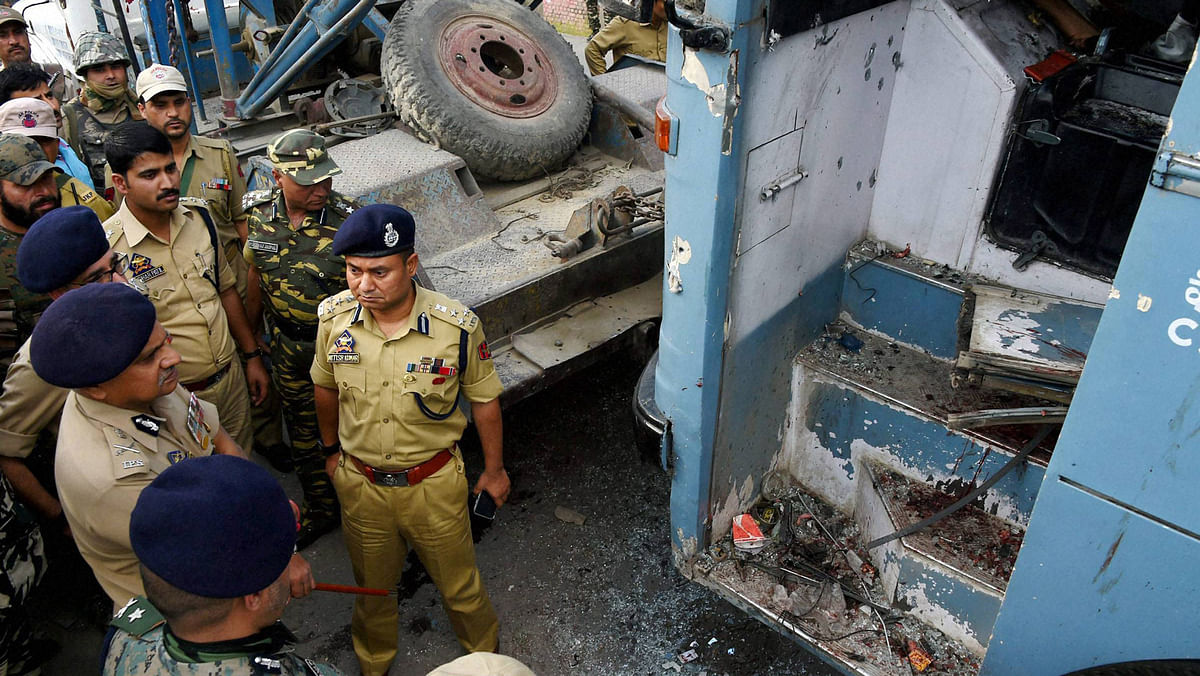 Security forces inspecting the CRPF bus attacked by LeT militants on the Srinagar-Jammu National Highway at Pampore in Srinagar, 25 June 2016. (Photo: PTI)
