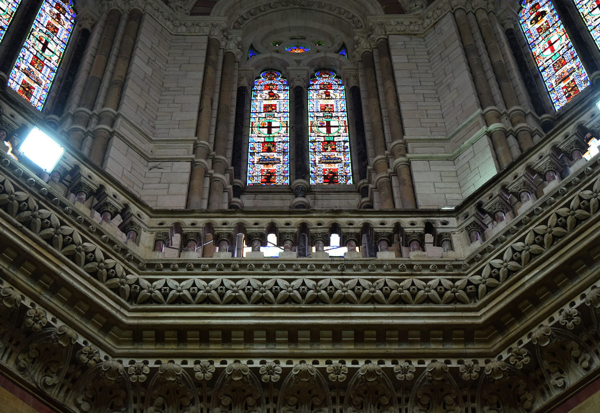Stained glass painted windows set in perfect symmetry and framed by laborious carvings is a feature that can be seen across Europe in cathedrals. These windows are placed in an octagon, as well; they lie just below the main ceiling of this hall. (Photo: <b>The Quint</b>/Pallavi Prasad)