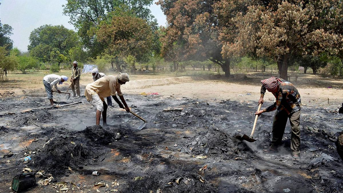 Workers clearing the ashes inside the clash-hit Jawahar Bagh in Mathura on Tuesday. (Photo: PTI)