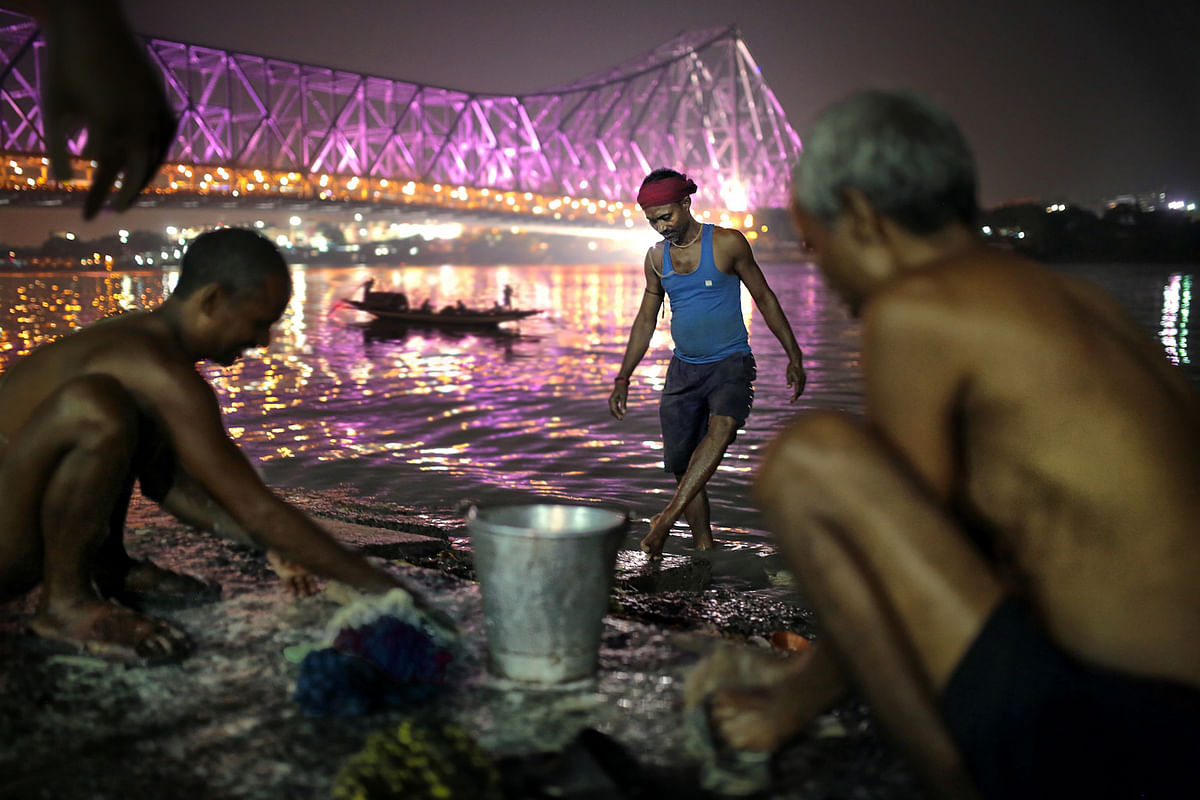 Fishermen wash their clothes and sing  trade songs by the banks of Ganges in Kolkata. (Photo: Souvid Datta)