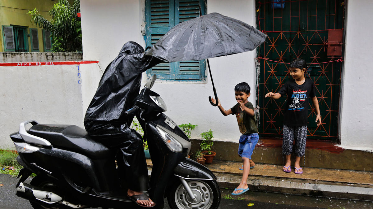 A child reaches to his father for an umbrella as it rains in Kolkata. ( Photo: AP)<a></a>