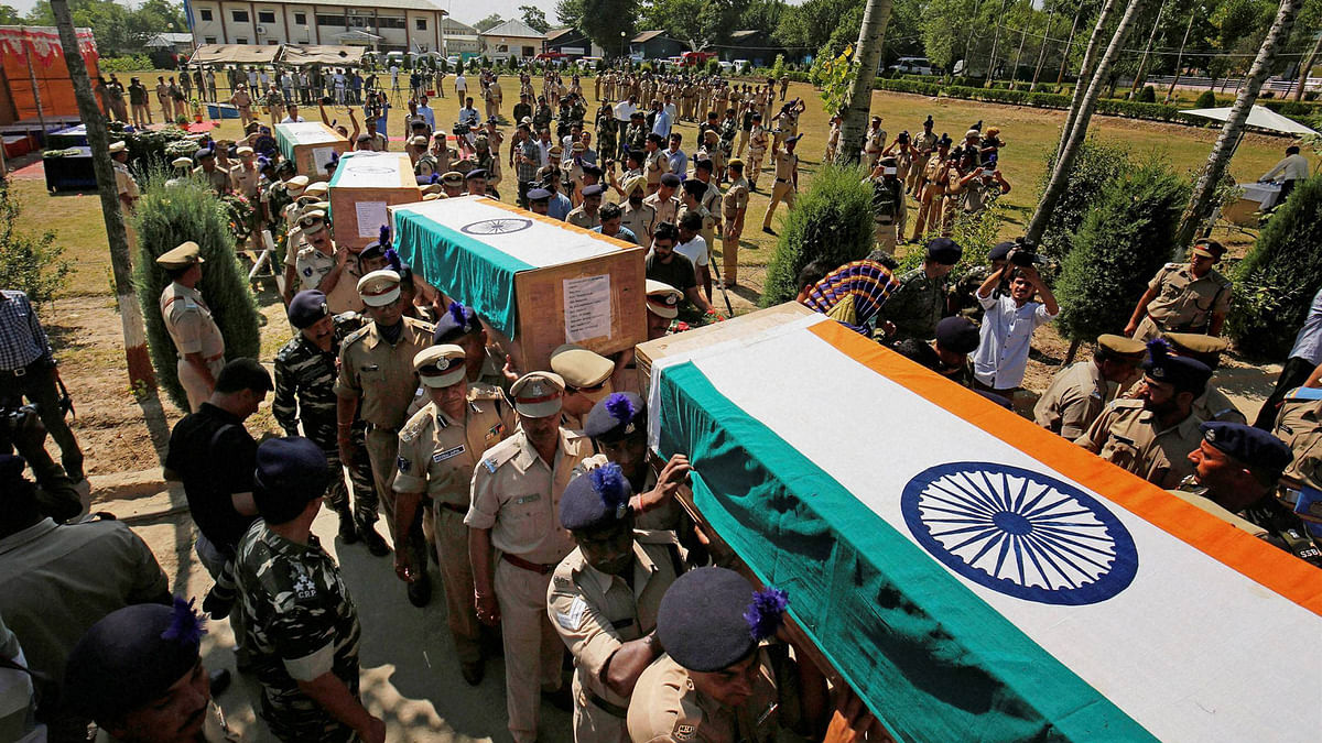 Senior police and CRPF officers carry makeshift coffins containing the  bodies of the slain troopers  after a wreath-laying ceremony at Humhama, on the outskirts of Srinagar, 26 June  2016. (Photo: PTI)