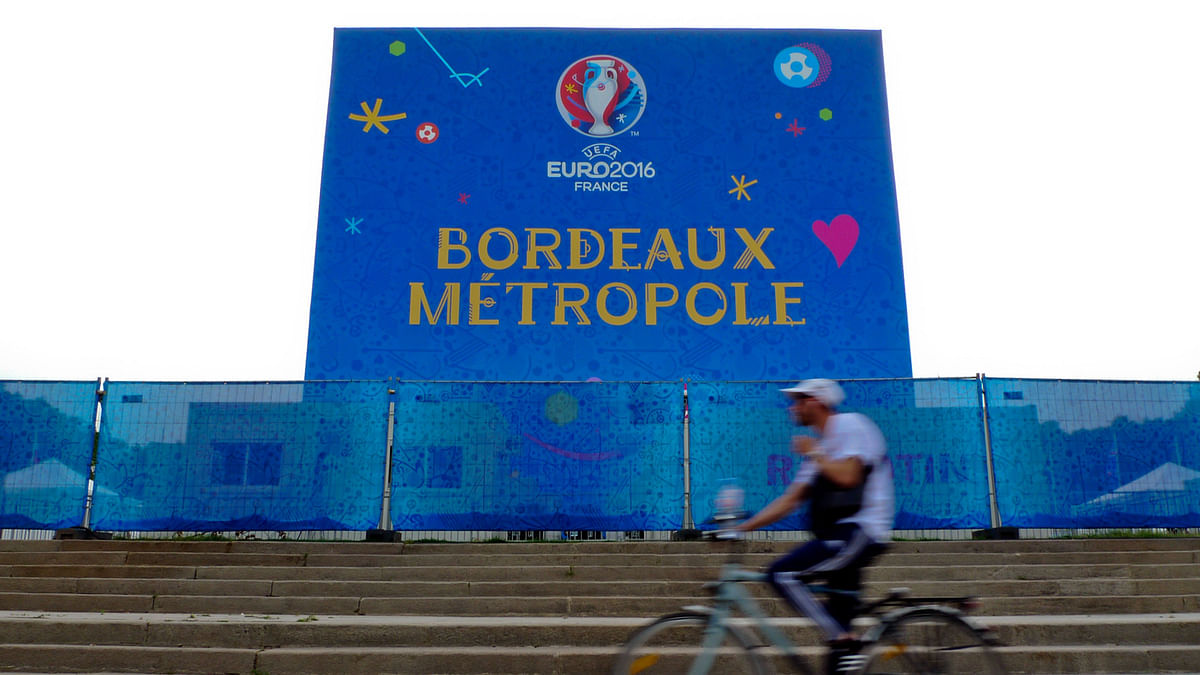 A man on a bicycle passes in front of a banner of the Euro 2016 soccer fans zone, in Bordeaux, France. ( Photo: AP)