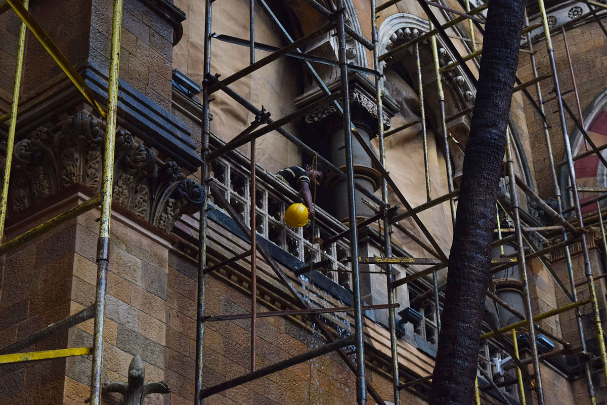 A man cleans the marble details in one of the balconies. Majority of the structure remains the same as was in 1888, with a few expansions to create more wings. (Photo: <b>The Quint</b>/Pallavi Prasad)