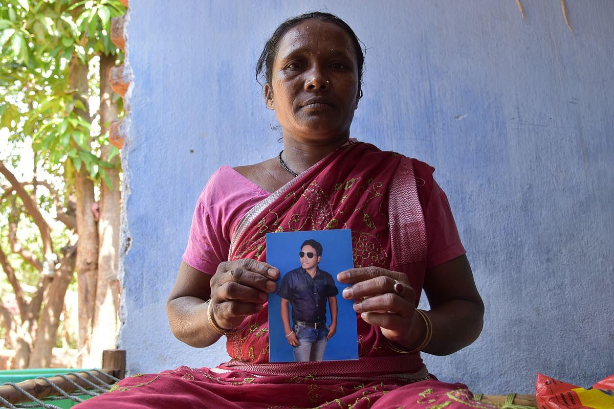 Sonaram Kisku's mother holding his photo. (Photo: Tanmoy Bhaduri)