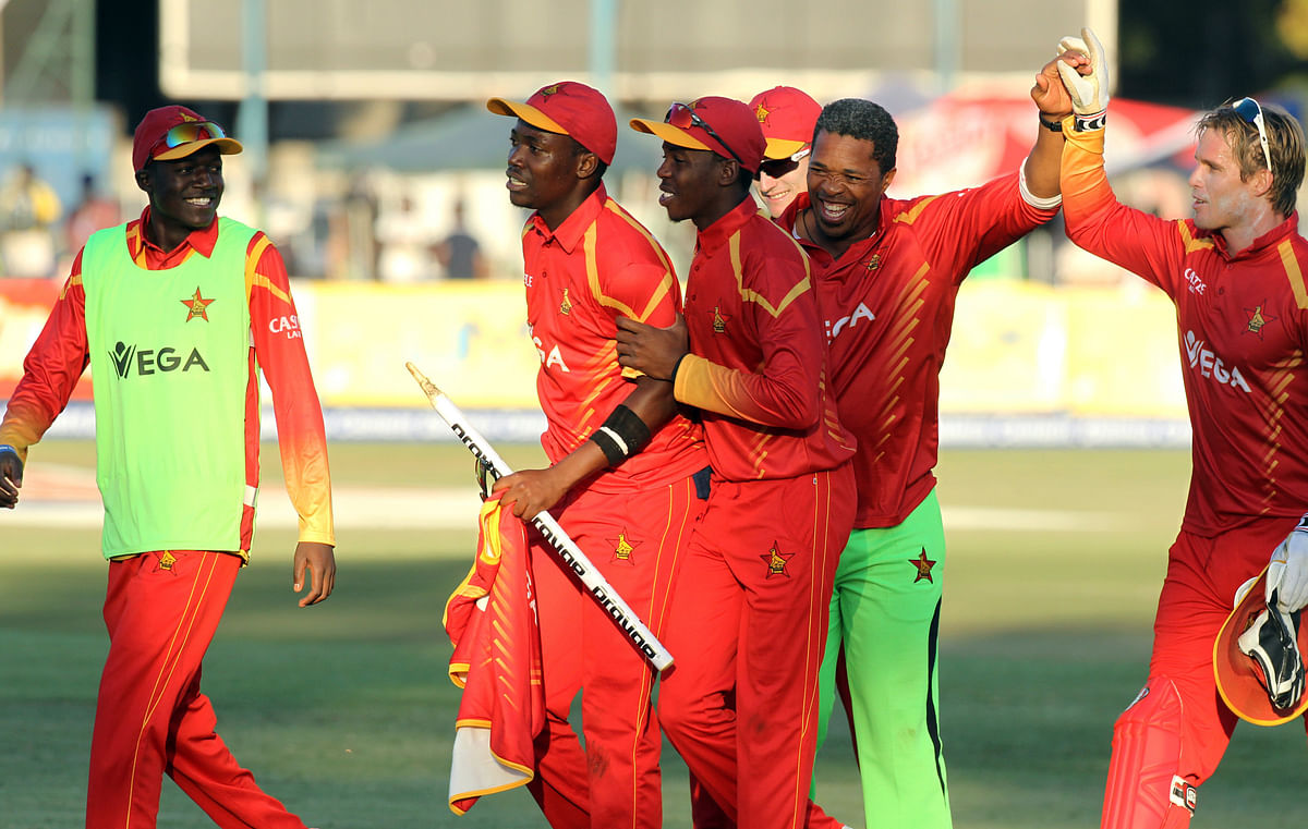 Zimbabwean players and their coach, Makhaya Ntini, second right, celebrate winning the T20 International cricket match against India at Harare Sports Club. (Photo: AP)