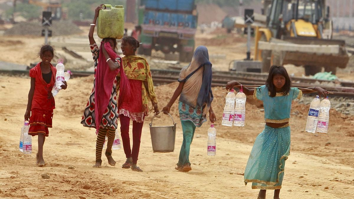 Young girls carry containers filled with drinking water beside the railway station in Agartala. (Photo: Reuters)