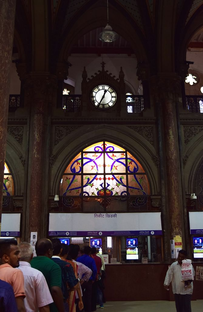 """Passengers queue up to purchase a """"VT return"""" below stained glass painted windows, red sandstone pillars and Victorian clocks. In 2008, 58 people were killed in an attack at VT and Taj Hotel (among other places). (Photo: <b>The Quint</b>/Pallavi Prasad)"""
