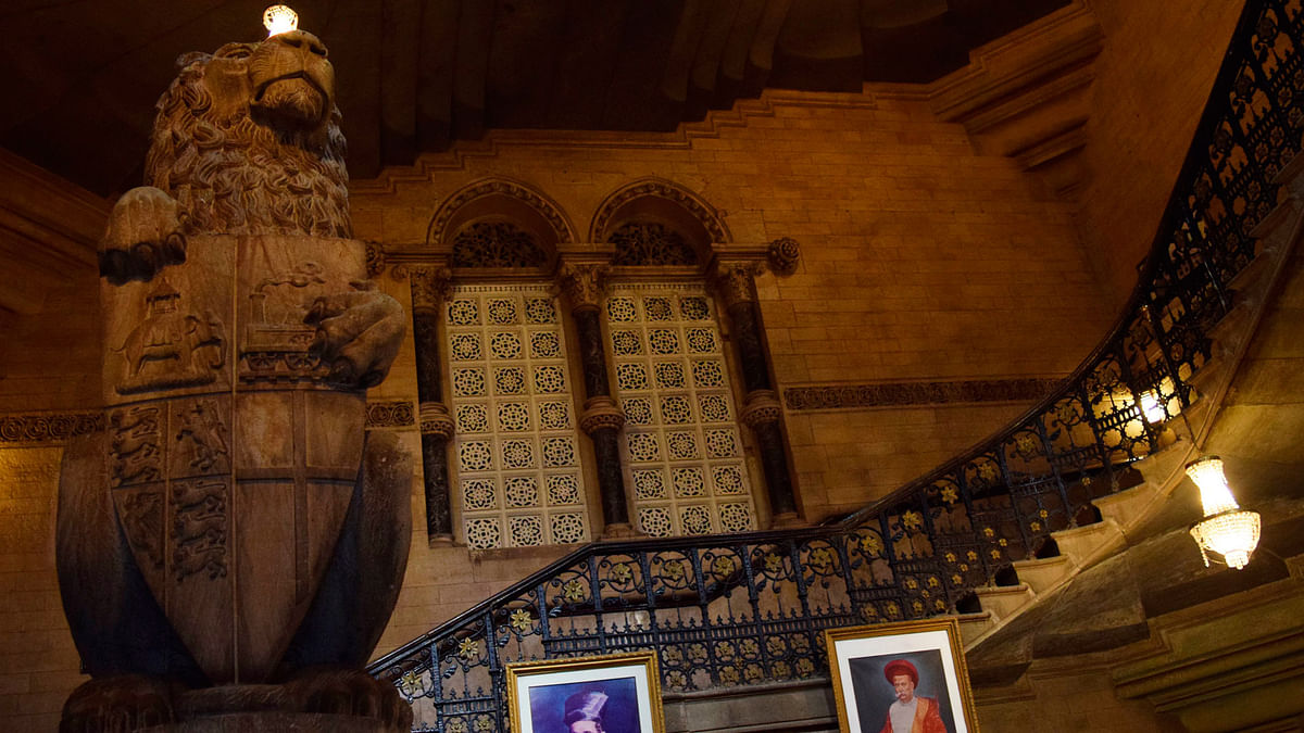 A stone statue of a lion bearing the coat of arms against spiralling staircases in incandescent light is the first glimpse of the decadence of this building, upon entering it. (Photo: <b>The Quint</b>/Pallavi Prasad)