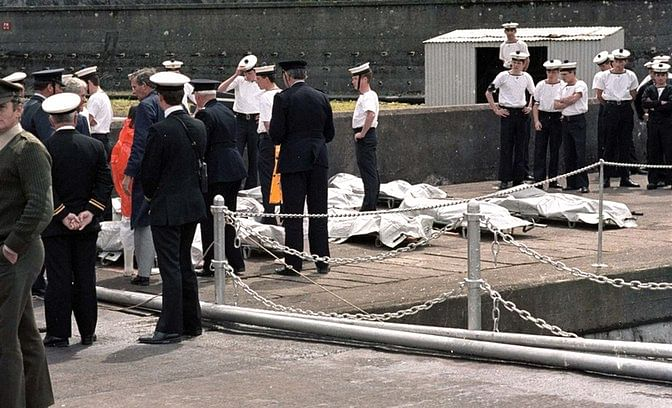 Officers, Irish sailors, and rescue workers look on as the 329 victims of the Air India jet are lined up on the docks in Cork, Ireland on 24 June 1985.