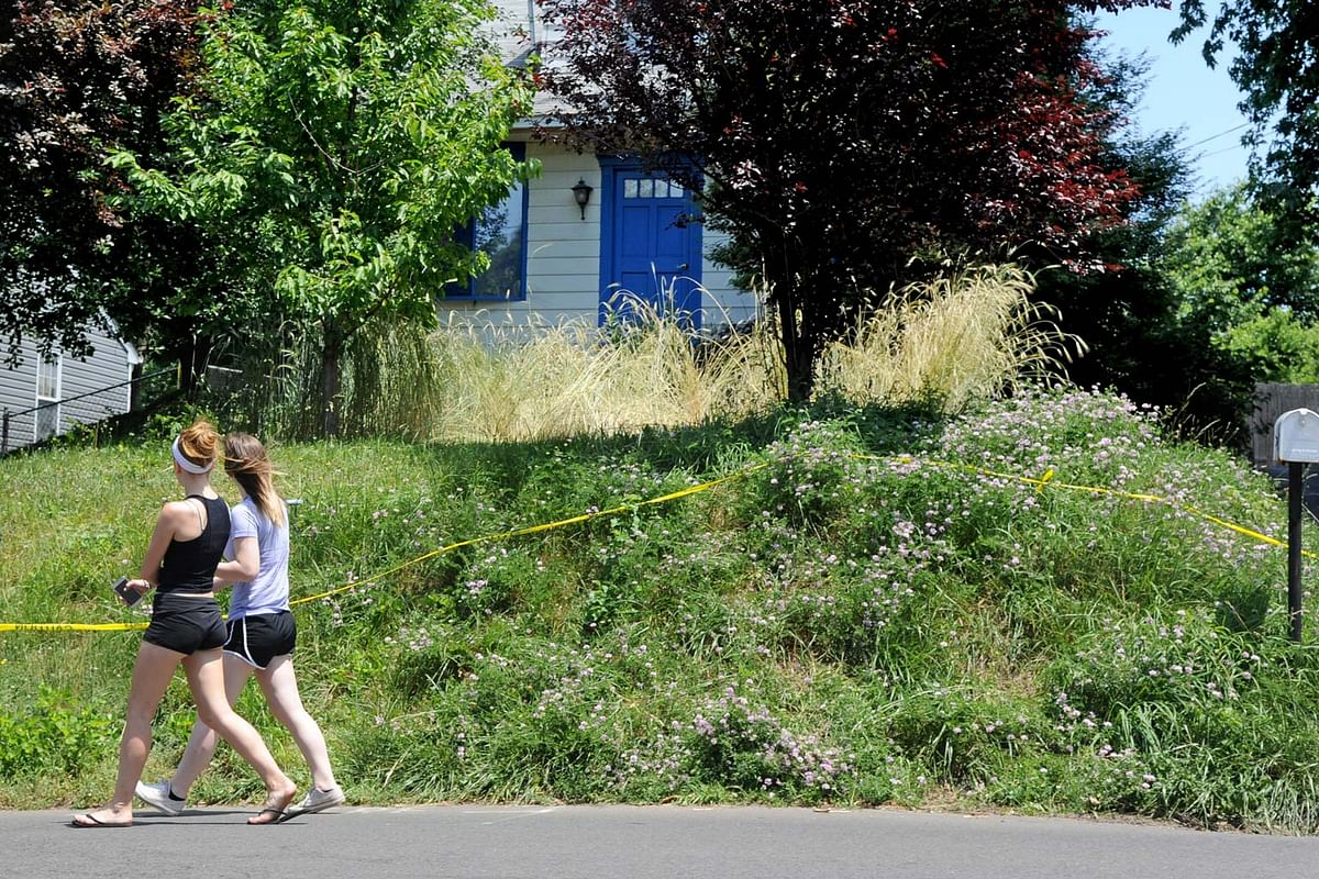 In this file photo from Saturday, 19 June 2016, two women walk past the home of Lee Kaplan in Feasterville, Pennsylvania. (Photo: AP)