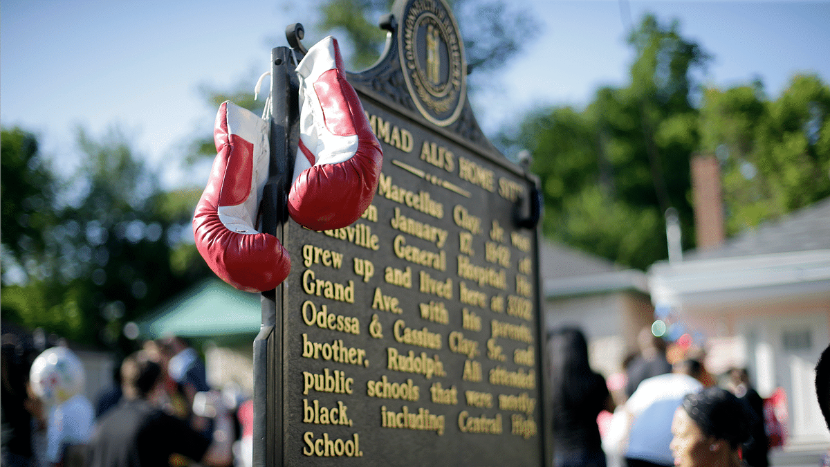 Boxing gloves hang on the historic site plaque in front of the boyhood home of Muhammad Ali as people wait for the arrival of his funeral procession Friday, June 10, 2016, in Louisville, Ky. (Photo: AP)