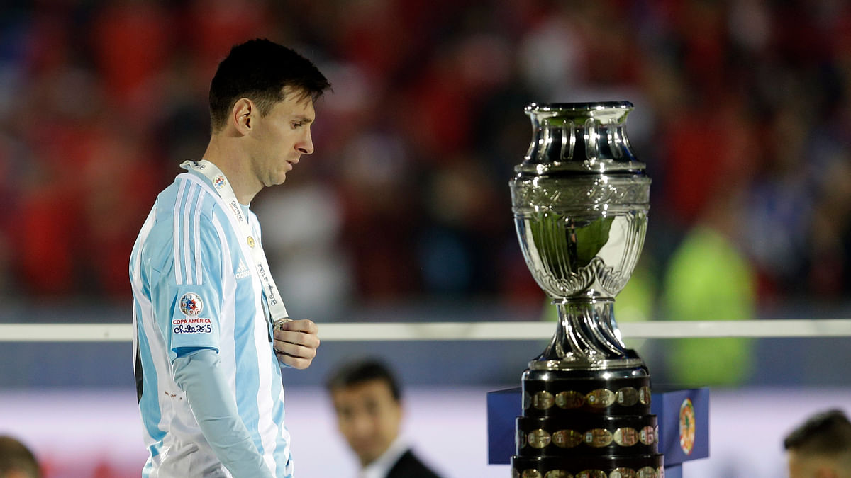 Lionel Messi takes a look at the winners trophy during the presentation ceremony. (Photo: AP)