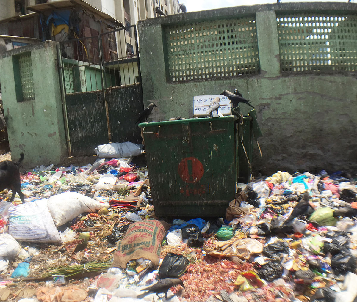 Garbage spilled around two trash cans outside a 'redeveloped' slum building in Nargis Nagar, Bandra (East), Mumbai. (Photo: <b>The Quint</b>/Pallavi Prasad)