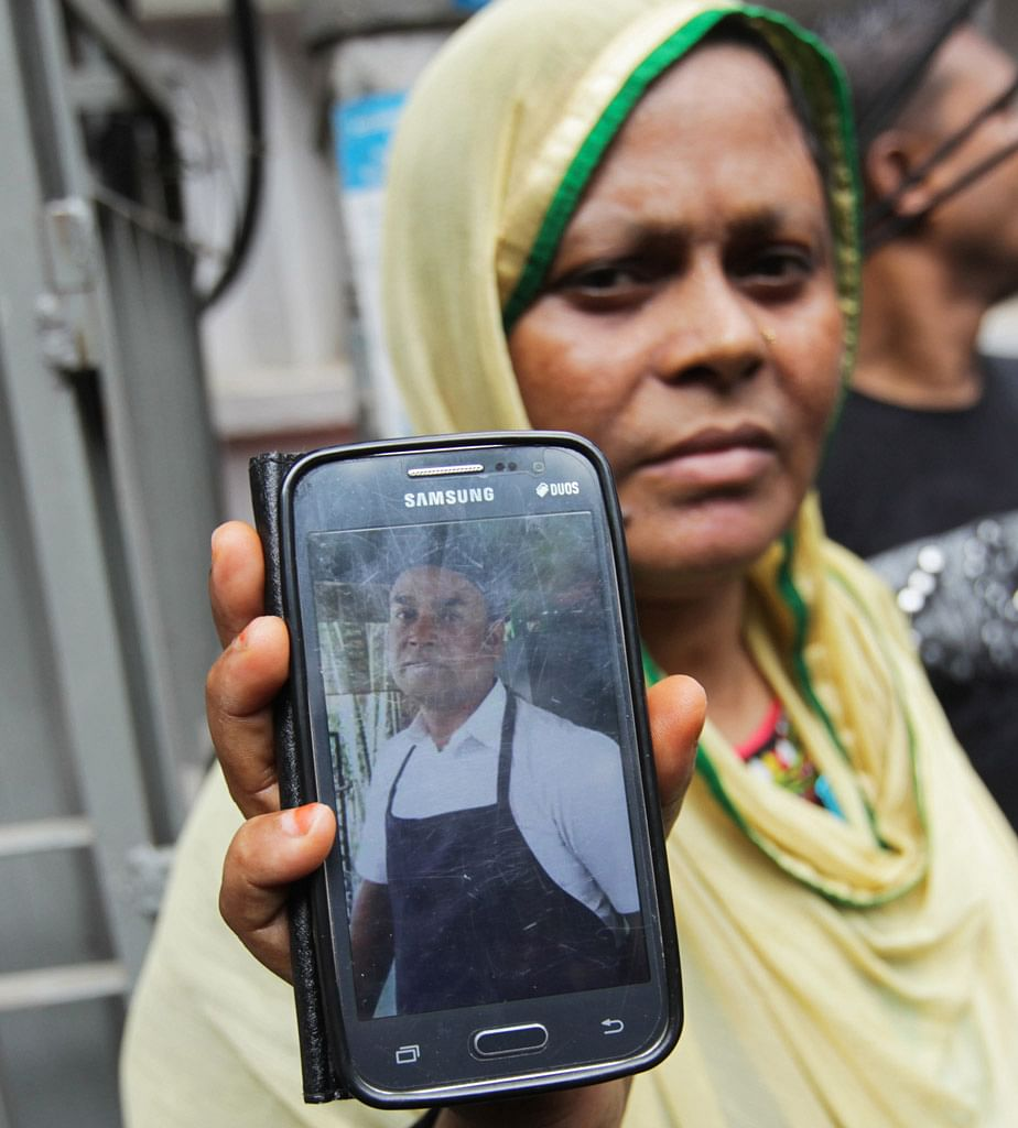 Johura Begum shows a photograph of her brother-in-law Saidul Islam, who works at the Holey Artisan Bakery and currently missing. (Photo: AP)