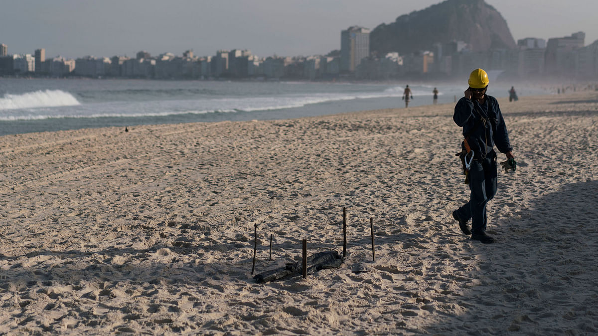 A construction worker of the Olympic beach volleyball venue observes a dismembered human foot covered with black plastic after it was found in front of the venue in Copacabana beach in Rio de Janeiro, Brazil.(Photo: AP)<a></a>